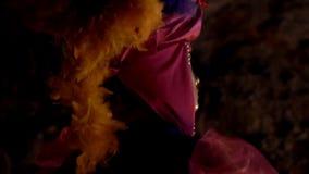 Twee meisjes in Carnaval-kostuums en maskers, een nachtdans door het licht van brand stock video