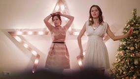 Twee meisjes dansen hebbend pret bij nieuwe jaarpartij Huisatmosfeer stock footage