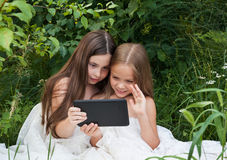 Twee meisjes die achter een computer spreken Stock Afbeeldingen