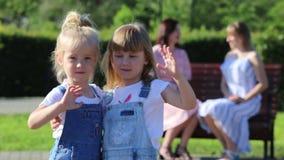 Twee meisjes die bij de camera golven terwijl hun mamma's spreken stock video