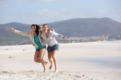 Twee meisjes die bij het strand lachen Stock Afbeelding
