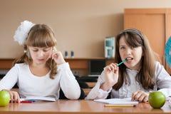 Twee meisjes die bij schoolbank zitten Royalty-vrije Stock Fotografie