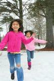 Twee meisjes die de sneeuw doornemen Stock Foto