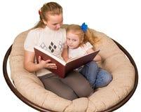 Twee meisjes die die boek lezen op wit wordt geïsoleerd royalty-vrije stock foto