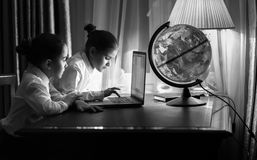 Twee meisjes die e-mail op laptop typen bij nacht Stock Afbeelding