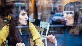 Twee meisjes die in een koffie spreken Royalty-vrije Stock Foto