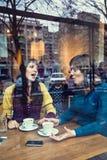 Twee meisjes die in een koffie spreken Stock Afbeeldingen