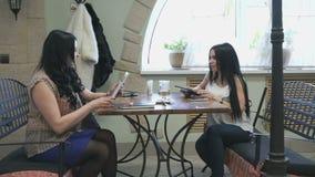 Twee meisjes die in een koffie spreken en drinken koffie stock videobeelden