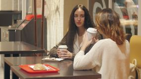 Twee meisjes die in een koffie spreken winkelen stock videobeelden