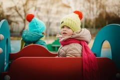 Twee meisjes die een stuk speelgoed auto berijden Stock Afbeeldingen