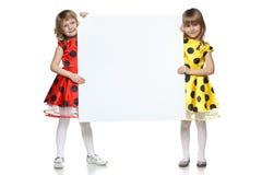 Twee meisjes die een whiteboard houden Stock Fotografie