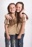 Twee meisjes die elkaar koesteren Stock Afbeeldingen
