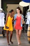 Twee meisjes die en bij winkelcomplex lopen spreken stock foto's