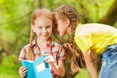 Twee meisjes die geheimen in het oor fluisteren stock afbeeldingen