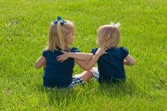 Twee Meisjes die in gras zitten Royalty-vrije Stock Fotografie