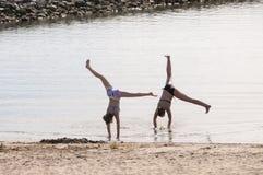 Twee meisjes die gymnastiek op het strand doen Stock Afbeelding