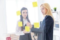 Twee meisjes die in het bureau spreken De meisjes zijn een dialoog dichtbij een transparante Raad met stickers royalty-vrije stock afbeelding