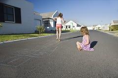 Twee Meisjes die Hinkelspels op Straat spelen Stock Foto's