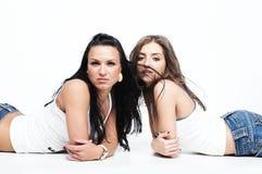 Twee meisjes die jeans op wit dragen Stock Afbeeldingen