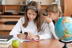Twee meisjes die in klaslokaal communiceren Stock Afbeelding
