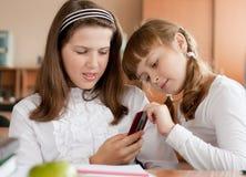 Twee meisjes die in klaslokaal communiceren Royalty-vrije Stock Foto