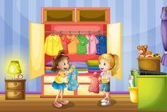 Twee meisjes die kleren kiezen van kast Stock Foto's