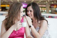 Twee meisjes die in koffie zitten Stock Foto's