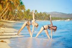 Twee meisjes die lichaamsbewegingen op een tropisch strand doen stock foto's