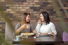 Twee meisjes die lunch hebben samen bij een restaurant Royalty-vrije Stock Afbeeldingen