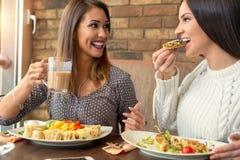 Twee meisjes die lunch hebben samen bij een restaurant Royalty-vrije Stock Afbeelding