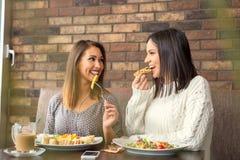 Twee meisjes die lunch hebben samen bij een restaurant Stock Afbeelding