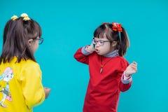 Twee meisjes die met benedensyndroom kleurrijke uitrustingen dragen stock afbeelding