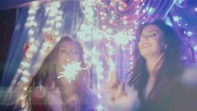 Twee meisjes die met Kerstmislichten dansen stock footage