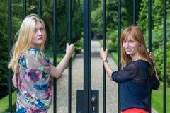 Twee meisjes die metaalbars van ingangspoort houden stock afbeeldingen