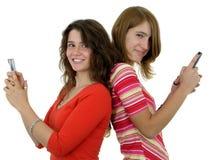 Twee meisjes die mobiele telefoons met behulp van Royalty-vrije Stock Afbeeldingen
