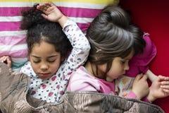 Twee meisjes die, multi rassenvriendschap samen slapen Stock Afbeeldingen
