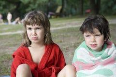 Twee meisjes die op bank van rivier zitten Stock Foto's