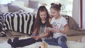 Twee meisjes die op bed het spelen met poppen zitten stock video