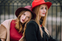 Twee meisjes die op de bank en de glimlach zitten Stock Foto's