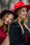 Twee meisjes die op de bank en de glimlach zitten Stock Afbeeldingen
