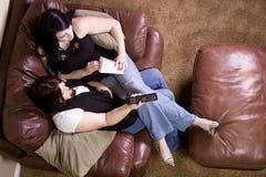 Twee Meisjes die op de Bank zitten die op een Film let Stock Afbeeldingen