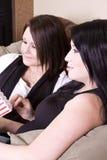 Twee Meisjes die op de Bank zitten die op een Film let Stock Fotografie