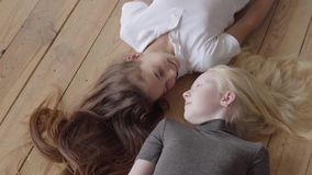 Twee meisjes die op de houten vloer liggen die elkaar bekijken Concept vriendschap Onbezorgde kinderjaren Echte mensen stock footage