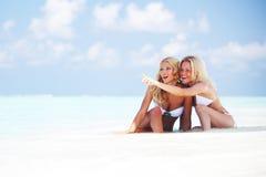 Meisjes die op oceaankust zitten Stock Fotografie