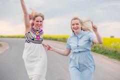 Twee meisjes die op de wegholding handen en het lachen in werking worden gesteld royalty-vrije stock foto