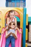 Twee meisjes die op dia in speelplaats zitten Stock Afbeeldingen
