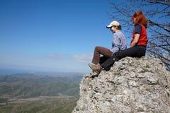 Twee meisjes die op een rots zitten stock afbeeldingen