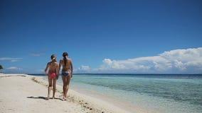 Twee meisjes die op een tropisch strand lopen stock footage