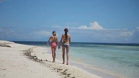 Twee meisjes die op een tropisch strand lopen stock video