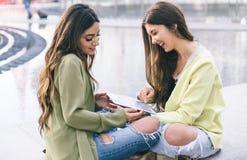 Twee meisjes die op grappige video's op de tablet letten Stock Fotografie
